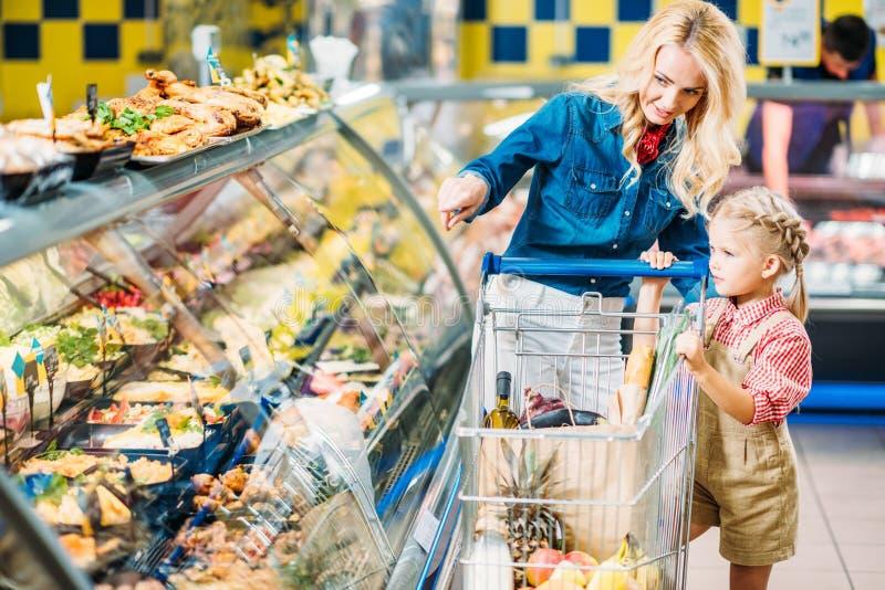 母亲和女儿有选择食物的购物台车的,当购物时 库存图片