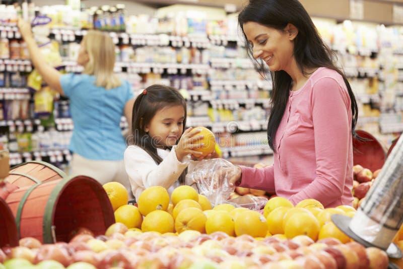母亲和女儿果子柜台的在超级市场 免版税库存图片