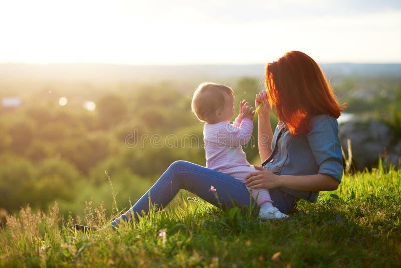 母亲和女儿消费家庭计时坐草,当日落时 库存图片