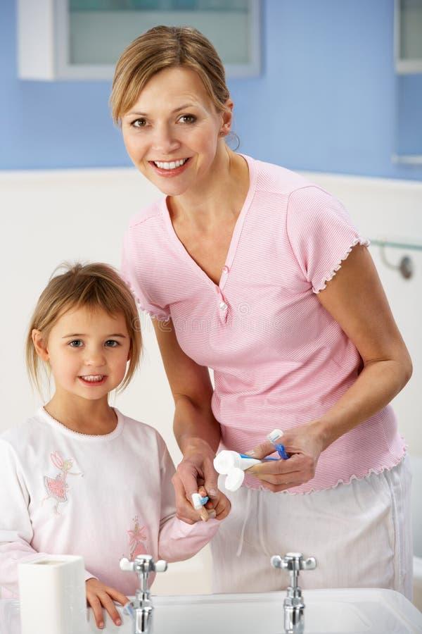 母亲和女儿清洁牙在卫生间里 免版税库存照片