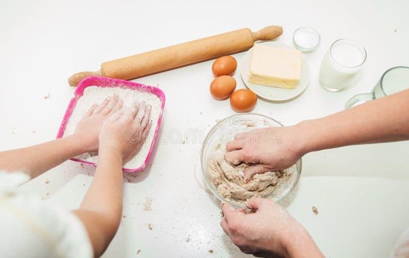 母亲和女儿的手揉比萨的面团 免版税库存照片