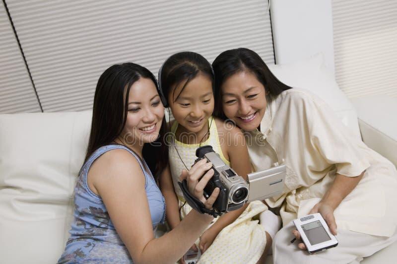 母亲和女儿看摄象机屏幕的沙发的 库存图片