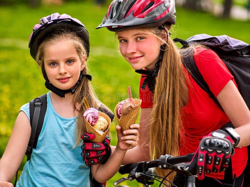 母亲和女儿自行车 吃冰淇凌,乘驾自行车的家庭 免版税库存图片