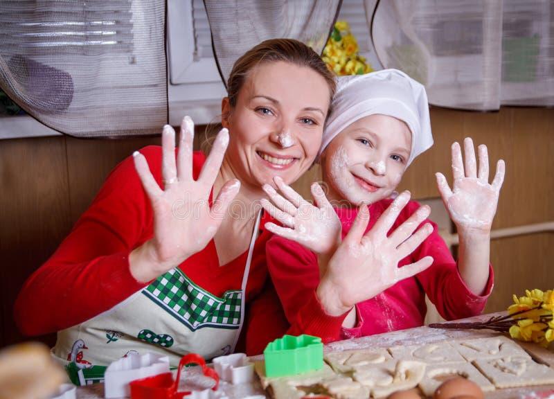 母亲和女儿获得乐趣在厨房 免版税库存照片