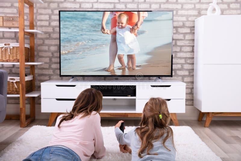 母亲和女儿观看的电视 免版税图库摄影