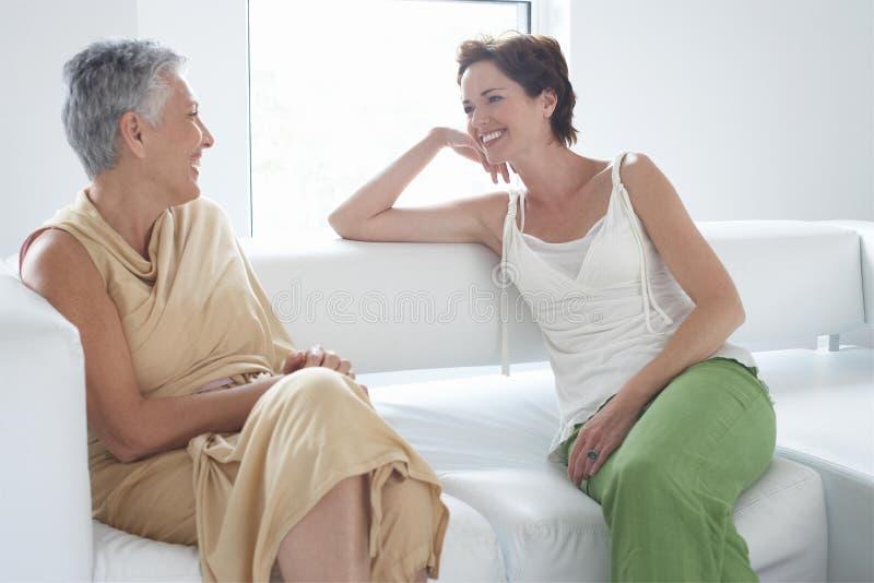 母亲和女儿谈话在沙发 免版税库存图片