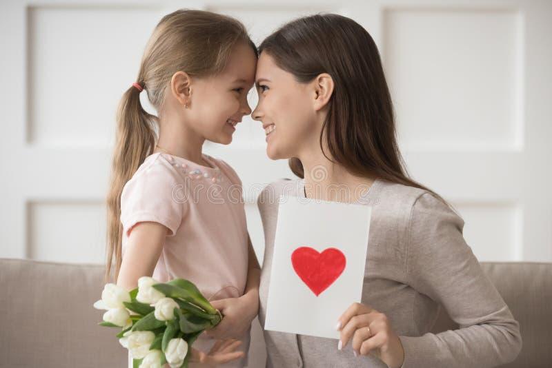 母亲和女儿轻轻地接触前额庆祝国际妇女的天 免版税库存图片
