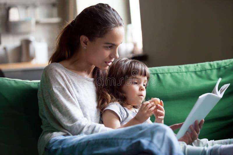 母亲和女儿阅读书在家坐沙发 免版税库存图片