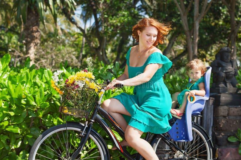 母亲和女儿骑自行车的和运载的花 免版税图库摄影