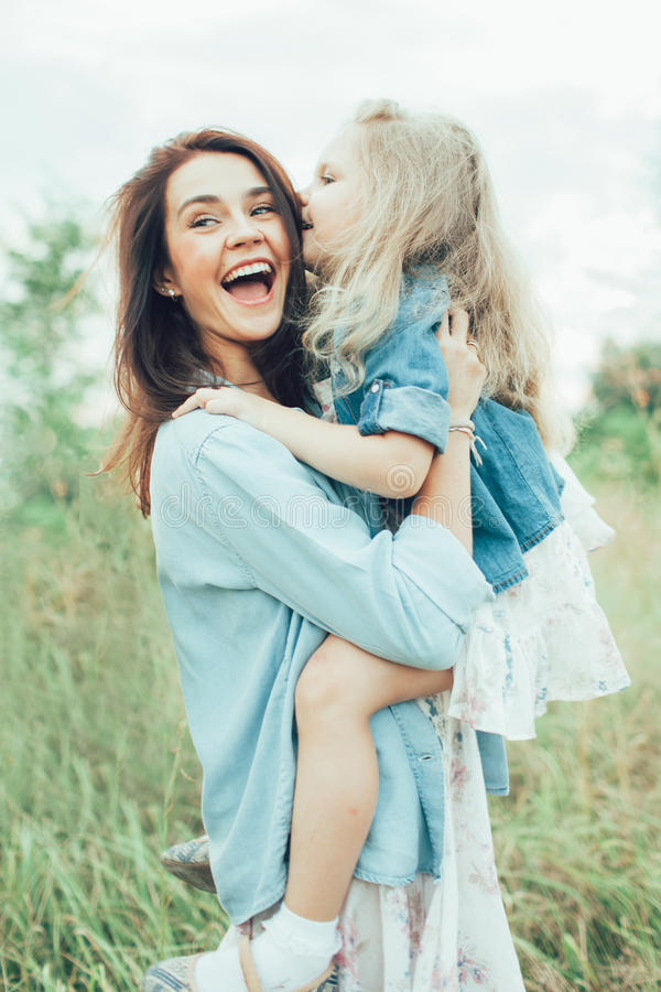 年轻母亲和女儿绿草的 库存照片