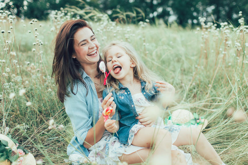 年轻母亲和女儿绿草的 免版税库存图片