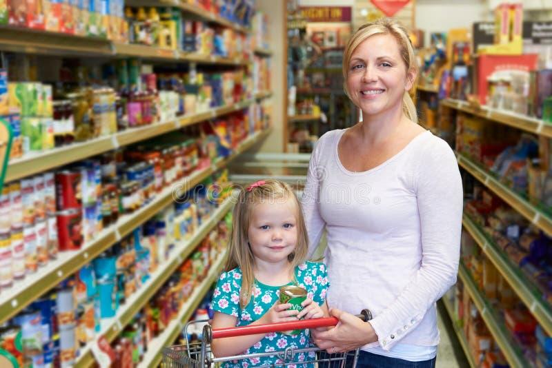 母亲和女儿画象在超级市场 库存图片