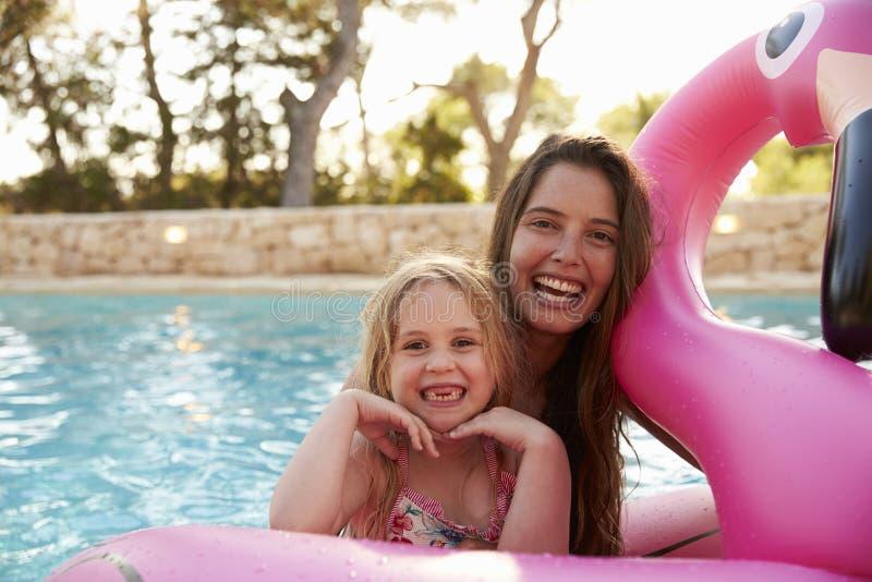 母亲和女儿Inflatables的在室外游泳池 免版税图库摄影