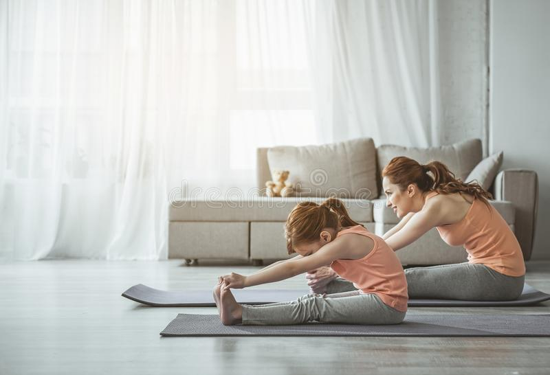 母亲和女孩做着在家舒展锻炼 免版税库存照片