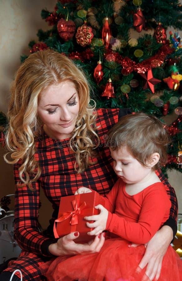 母亲和女婴在圣诞树下与礼物箱子 免版税库存照片