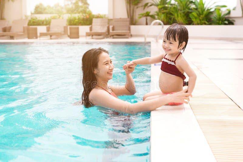 母亲和女婴获得乐趣在水池 暑假和 免版税库存图片