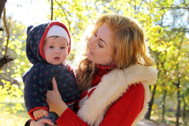 母亲和女婴谈话在秋天停放 免版税库存图片