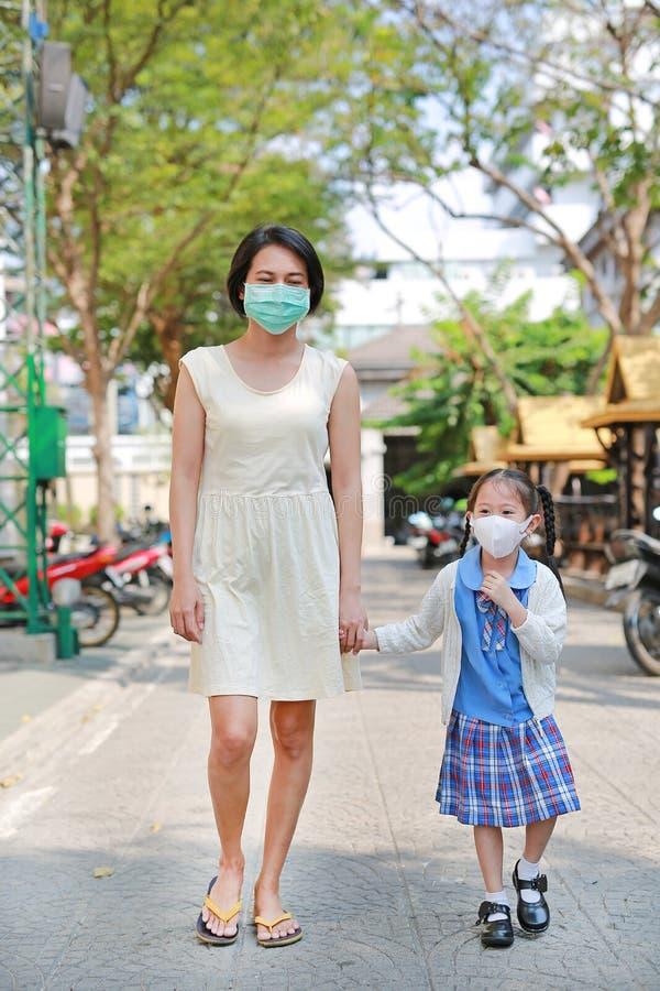 母亲和她女儿走去教育与戴着保护面具反对PM 2 r ?? 库存图片