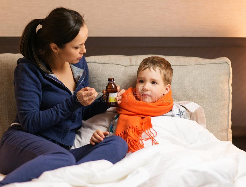 母亲和她病的儿子 免版税库存图片