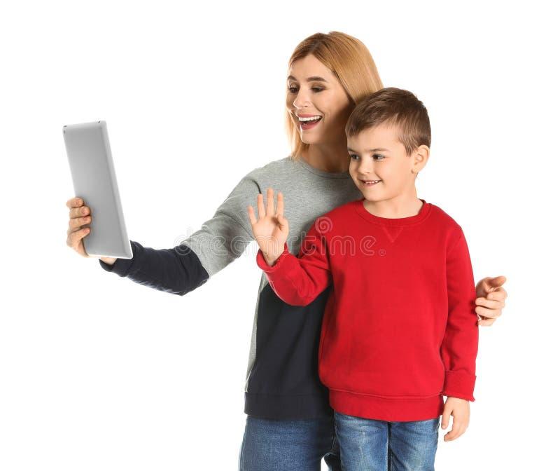 母亲和她的使用在片剂的儿子视频聊天 免版税图库摄影