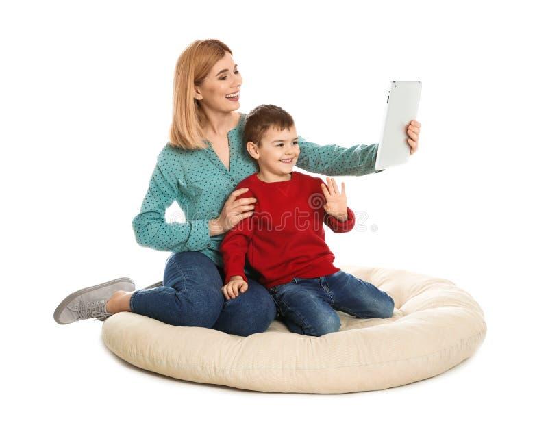 母亲和她的使用在片剂的儿子视频聊天 免版税库存图片