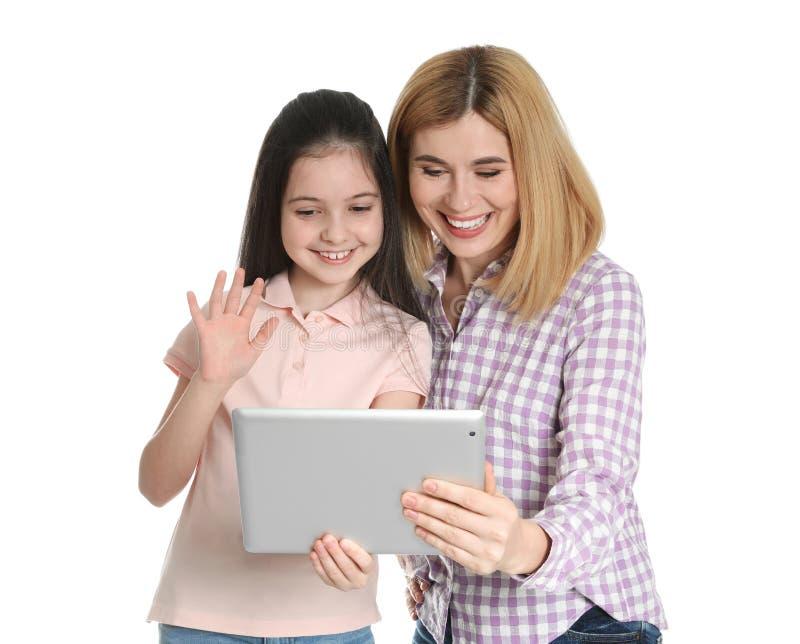 母亲和她的使用在片剂的女儿视频聊天 图库摄影
