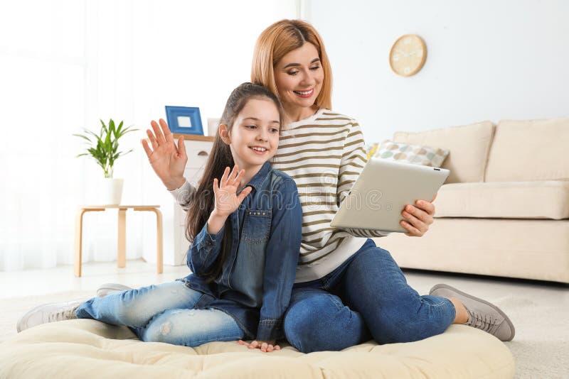 母亲和她的使用在片剂的女儿视频聊天 免版税库存图片