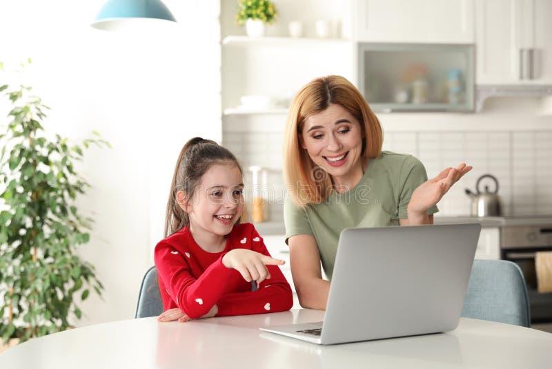 母亲和她的使用在膝上型计算机的女儿视频聊天在桌 图库摄影