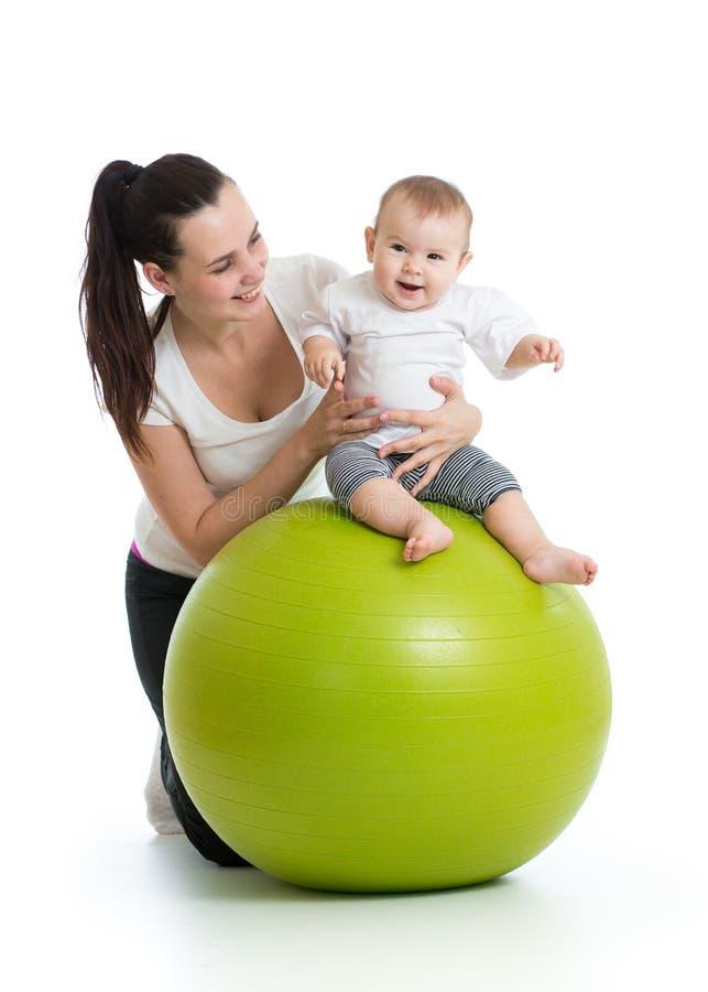 年轻母亲和她的做在体操球的小婴儿瑜伽锻炼被隔绝在白色 免版税库存图片