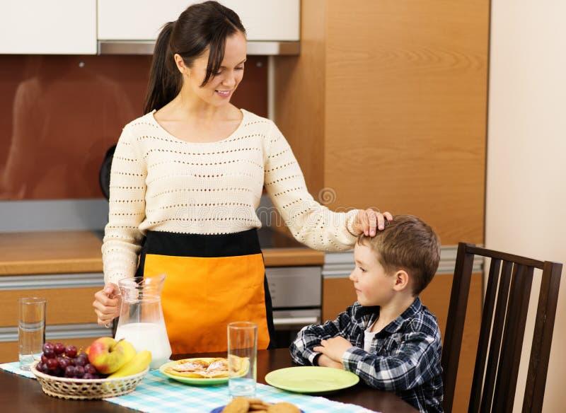 年轻母亲和她的儿子厨房的 库存图片