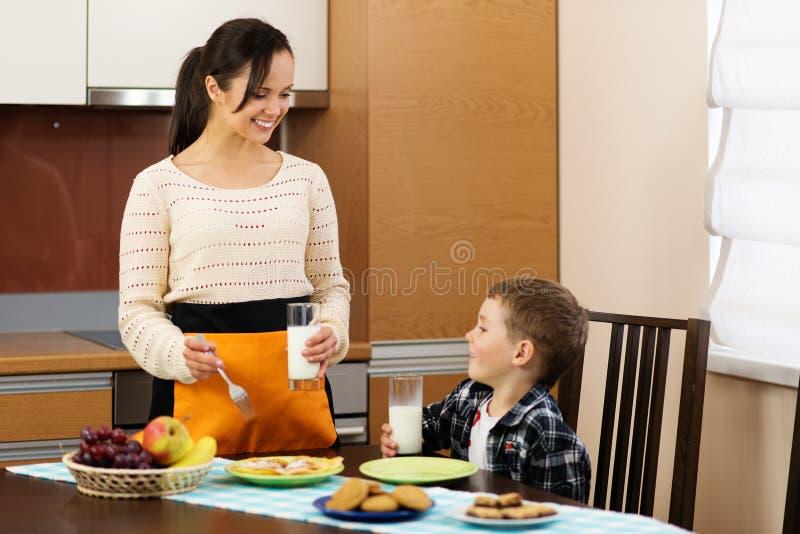 年轻母亲和她的儿子厨房的 库存照片