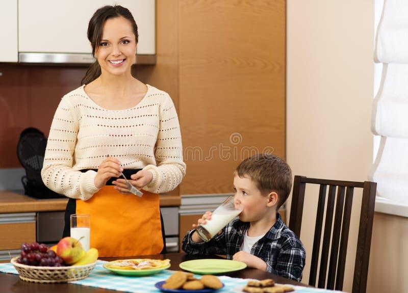 年轻母亲和她的儿子厨房的 免版税库存图片
