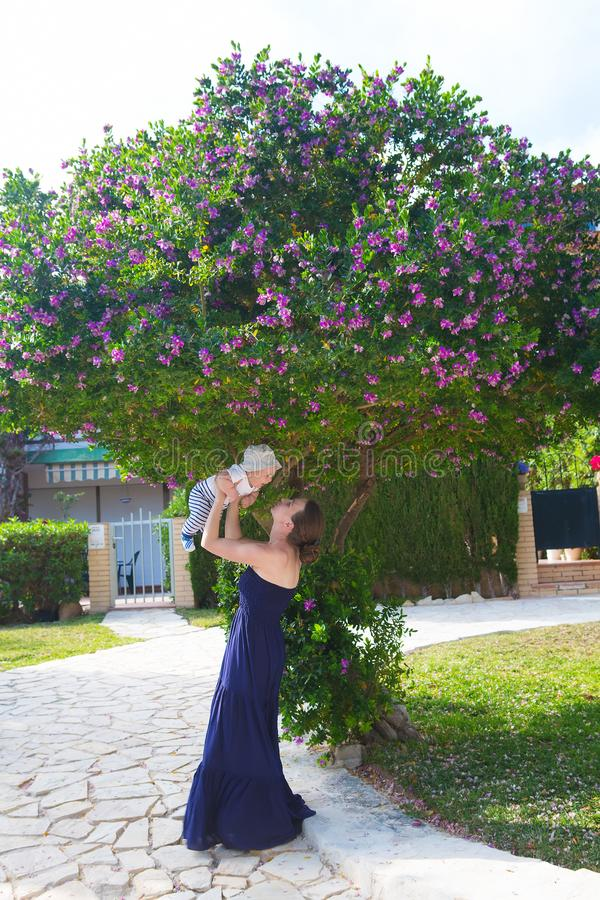 母亲和她的儿子在开花的树下 免版税库存照片