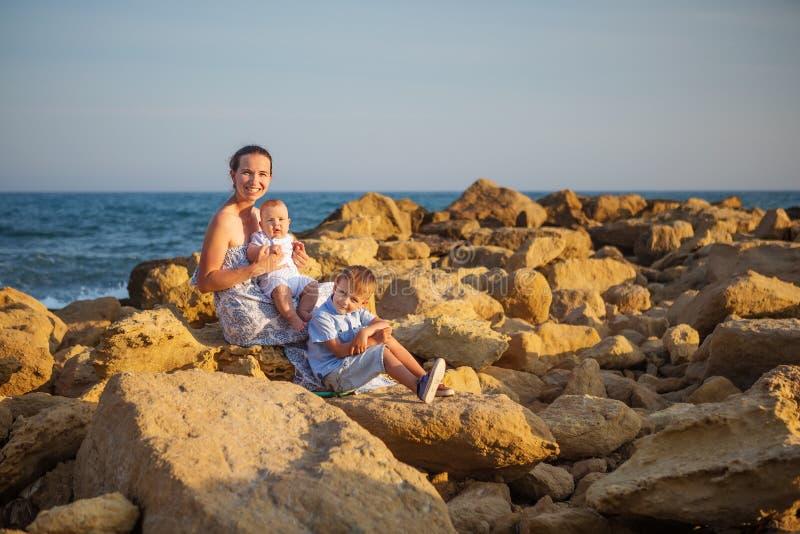 母亲和她的儿子获得乐趣在海海滩在日落 库存图片