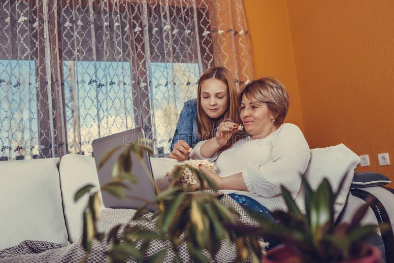 母亲和她的十几岁的女儿是电影和吃玉米花 免版税库存照片