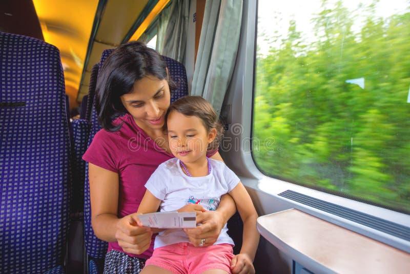 母亲和她的女儿享受火车旅行 免版税库存照片
