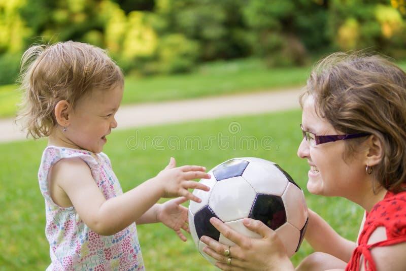 母亲和她的女儿使用与橄榄球球在公园 免版税库存图片