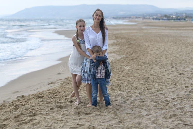 母亲和她的女儿和儿子海滩的 图库摄影