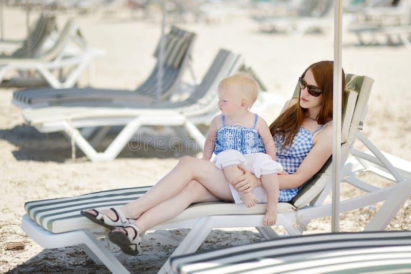 年轻母亲和她的女儿坐sunbed的  库存照片