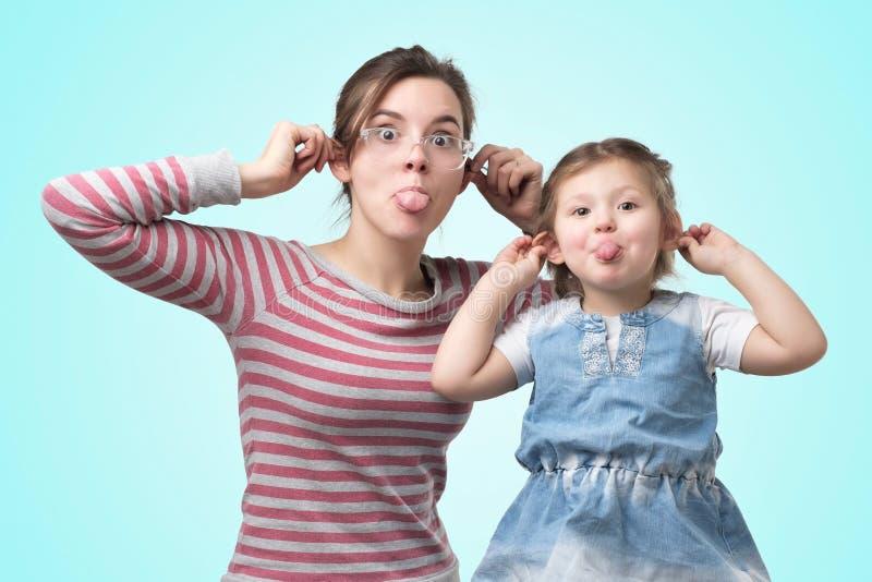 母亲和她的女儿女孩陈列猴子鬼脸 免版税库存照片