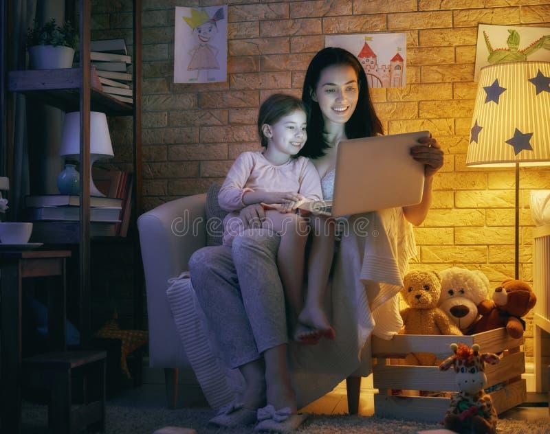 母亲和她的女儿有膝上型计算机的 库存照片