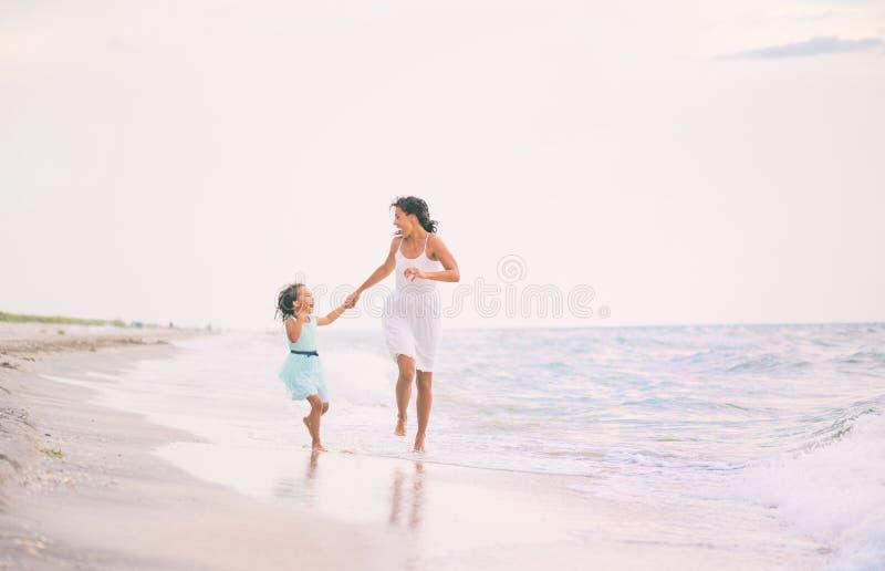 母亲和她的女儿赛跑和有乐趣在海滩 免版税图库摄影