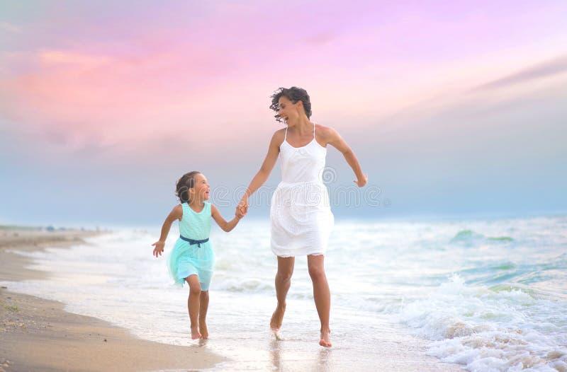 母亲和她的女儿赛跑和有乐趣在海滩 库存图片