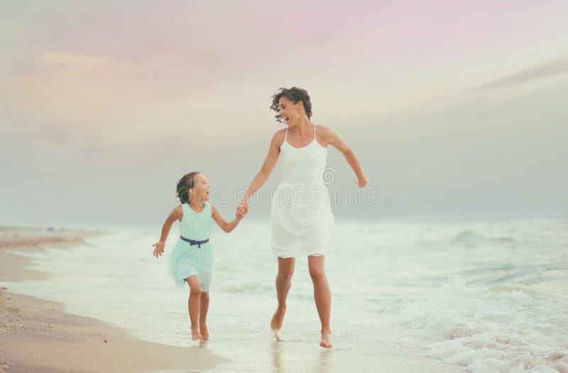 母亲和她的女儿赛跑和有乐趣在海滩 免版税库存照片