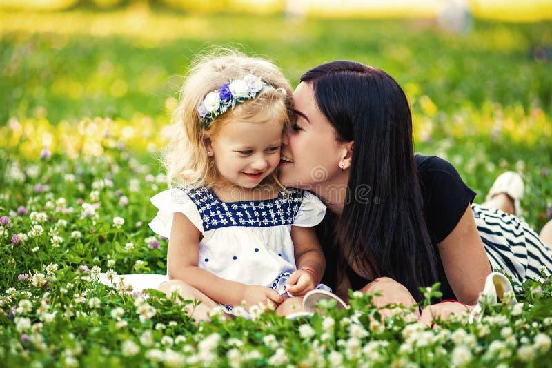 母亲和她的孩子享受早期的春天,吃苹果,愉快 库存图片