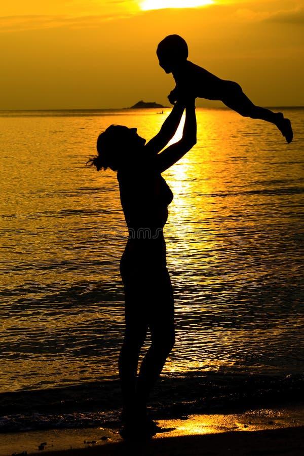 母亲和她的孩子剪影 图库摄影