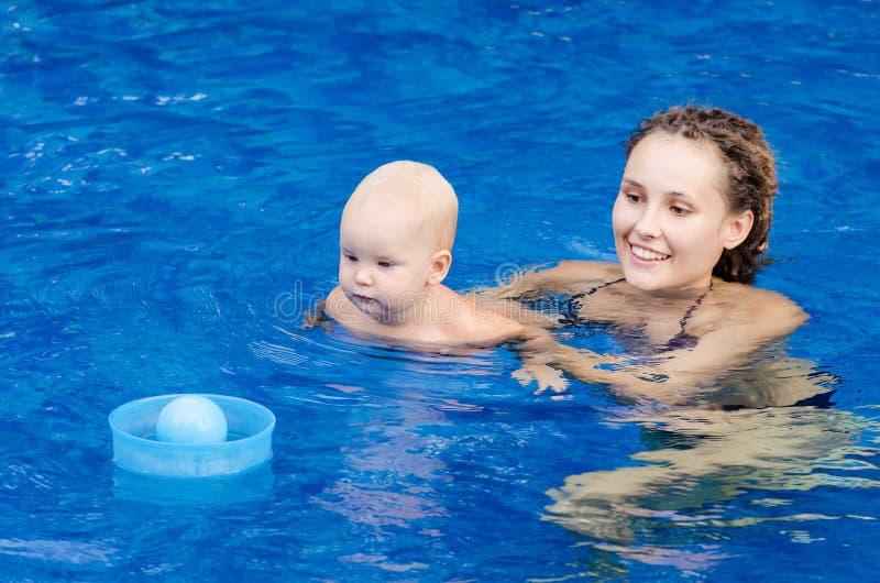母亲和她的孩子水池的 使用与与他的小女儿的一个球的妇女 免版税库存图片