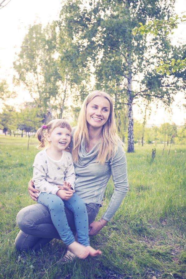 年轻母亲和她的小女儿在公园享有生活 免版税库存照片
