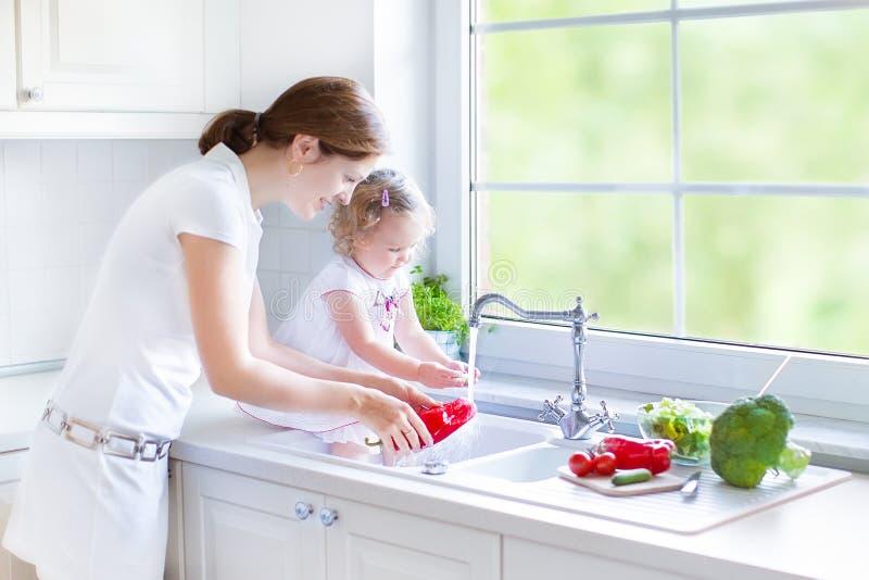 母亲和她的小孩女儿洗涤的菜 图库摄影