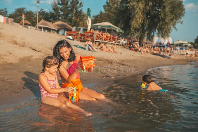 母亲和她的小愉快的女儿在水中使用与海滩玩具 免版税库存图片